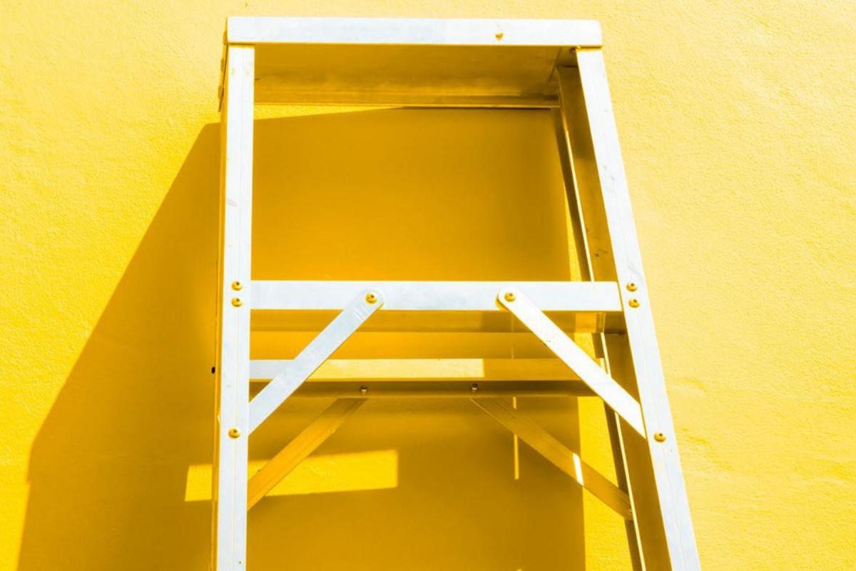 Das Bild zeigt eine Leiter vor einem gelben Hintergrund