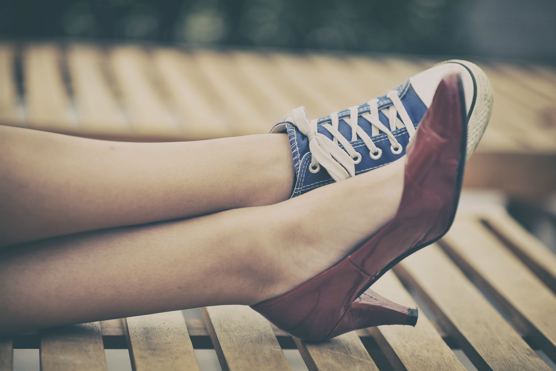 Woman legs in different shoes - Highheels und Turnschuhe