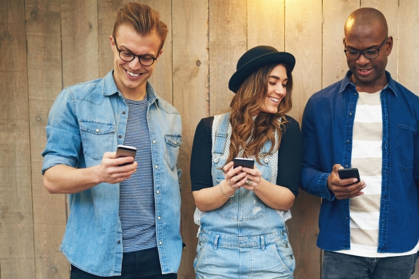 Group of young people men and women in casual wear standing against unpainted wooden wall, looking at smartphones and smiling
