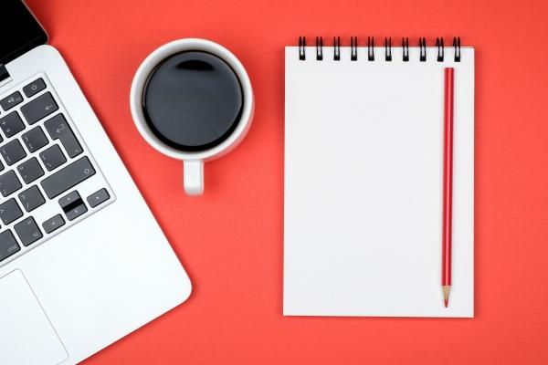 Das Bild zeigt Schreibunterlagen wie Laptop und Block auf rotem Untergrund.