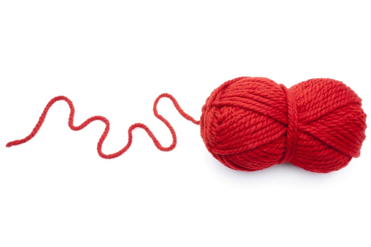 Auf dem Foto ist ein roter Wollknäuel zu sehen, der symbolisch für einen roten Faden steht.