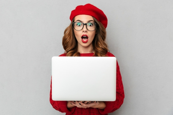 Das Bild zeigt eine junge Frau in einem roten Outfit mit Laptop in der Hand und erstauntem Gesichtsausdruck