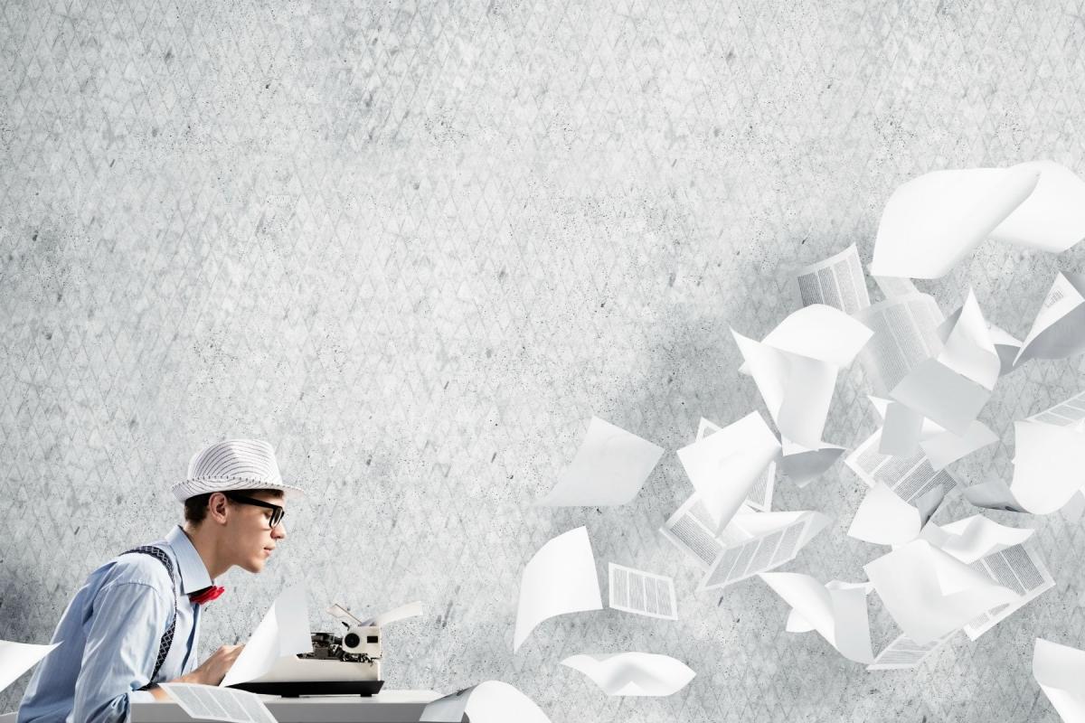 Das Bild zeigt einen Jungen Mann an der Schreibmaschine und Blätter, die durch den Raum fliegen.