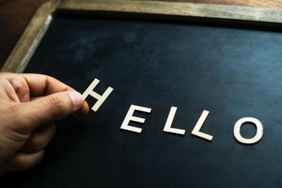 Das Foto zeigt eine kleine Schultafel auf die jemand die Buchstaben HELLO legt.