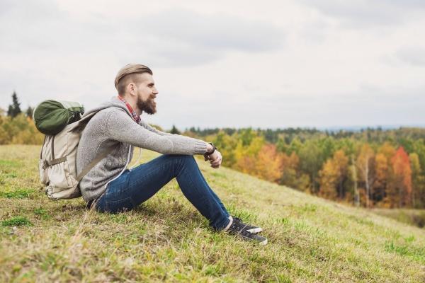 Das Bild zeigt einen Mann, der auf einer Wiese sitzt und in die Ferne blickt.
