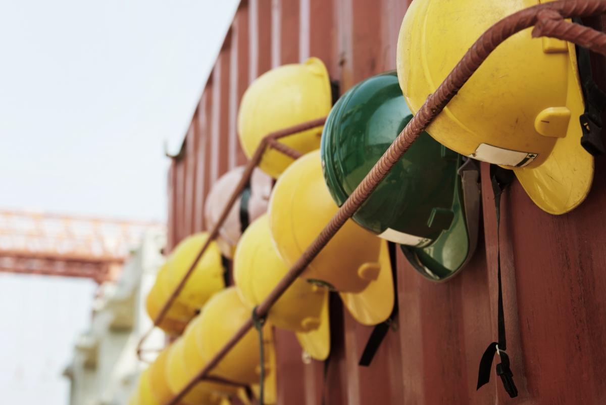 Das Bild zeigt gelbe Bauhelme und dazwischen befindet sich ein grüner Bauhelm
