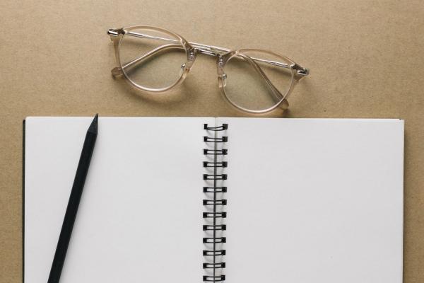 Leeres Notizbuch mit Stift und Brille