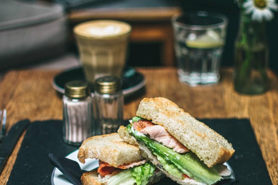 Das Bild zeigt ein Sandwich und eine Tasse Kaffee im Hintergrund